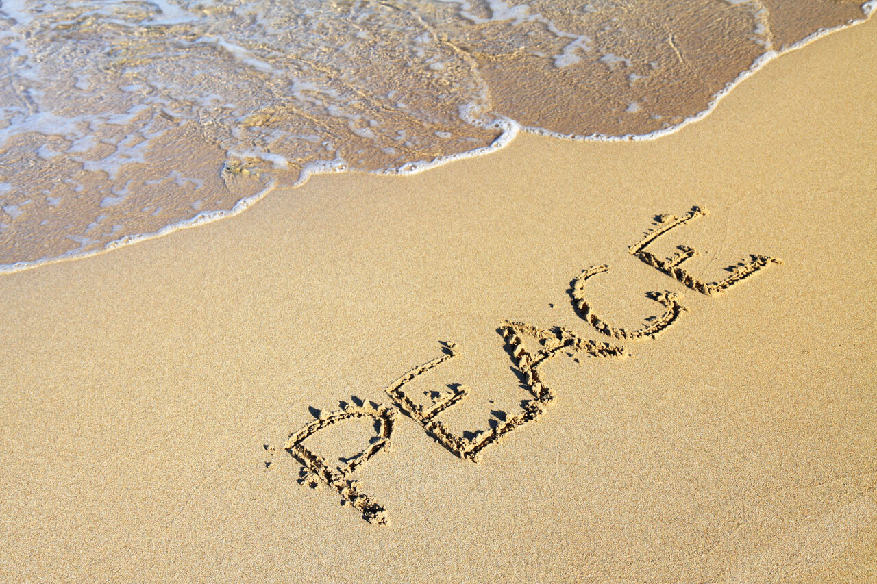 international world peace day text on sand